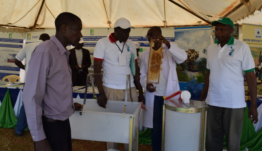 Edward Alitsi, VCDO Executive Director (R) onlooking as one of VCDO Staff exhibiting what they do in Beekeeping during Nile Day 2016/ Photo NBD